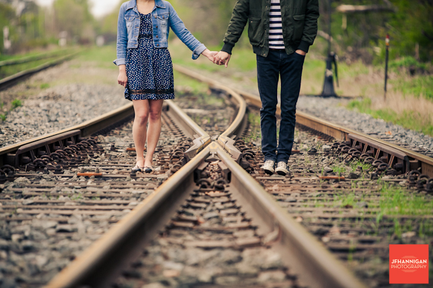 couple holds hands on train tracks