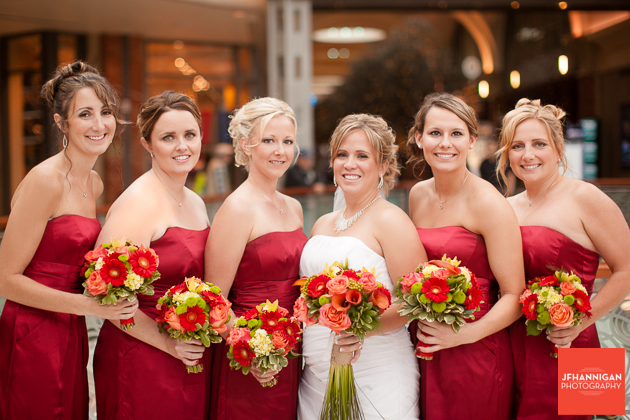 bride with bridal party in red dresses with fall colored flowers