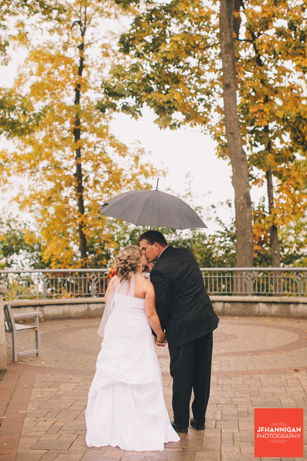 bride and groom kissing under umbrella with fall colored trees in background