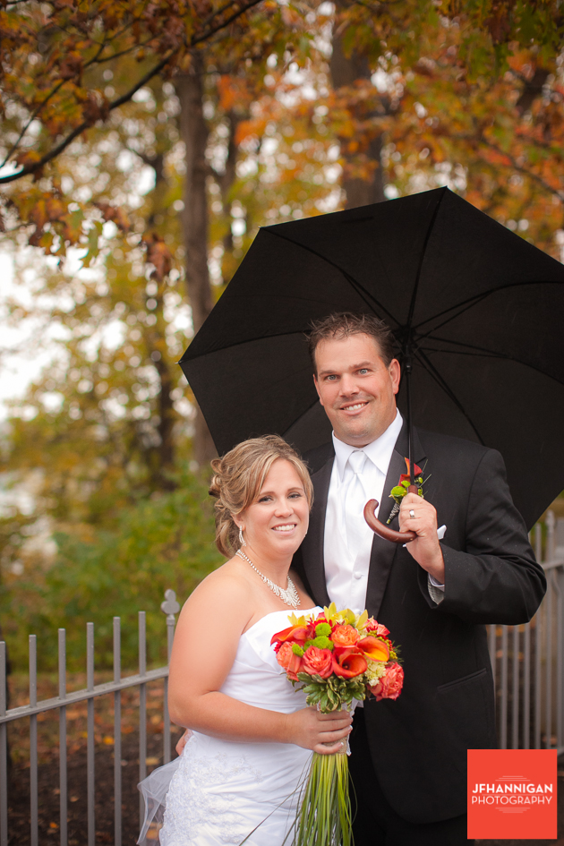 bride and groom under umbrella with fall colored folliage in background