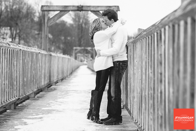 black & white photo couple on wooden railed bridge