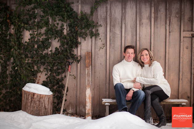 couple sitting in front wood slat buiding in the snow