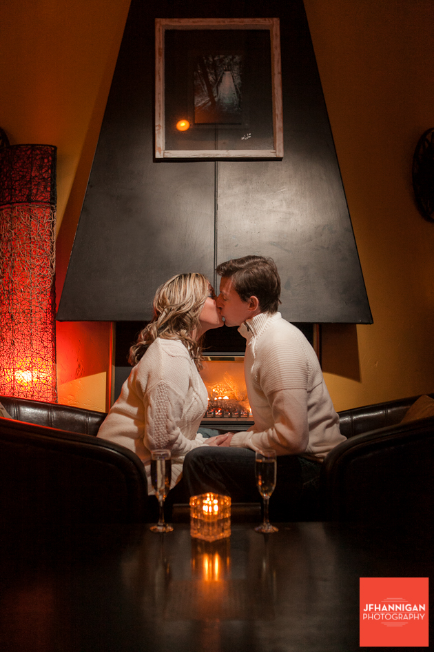 couple kissing  on leather chairs candle in foreground