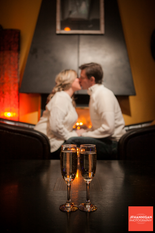 couple kissing in background wine glasses and candle in foreground