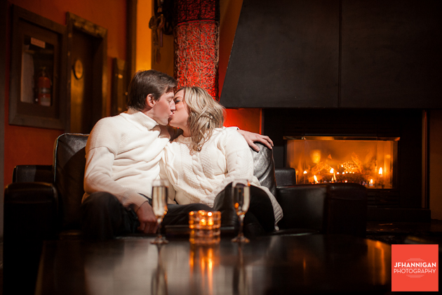 couple kissing with fireplace in background Engagement shoot