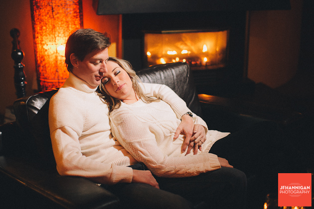 couple relaxing on sofa fireplace in background