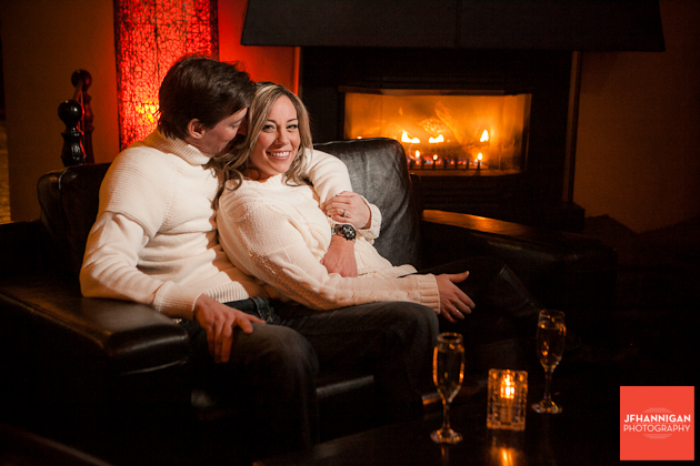 couple sitting in front of fireplace wine glasses and candle in foreground