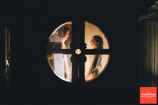 couple through circular window Niagara wedding photographer engagement shoot