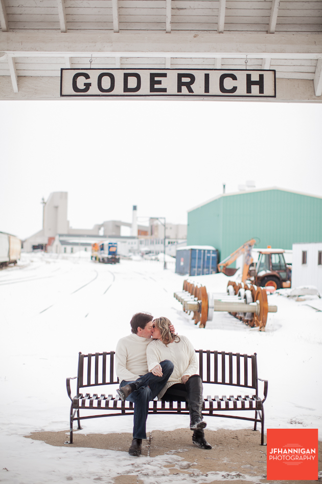couple kissing on bench in snow