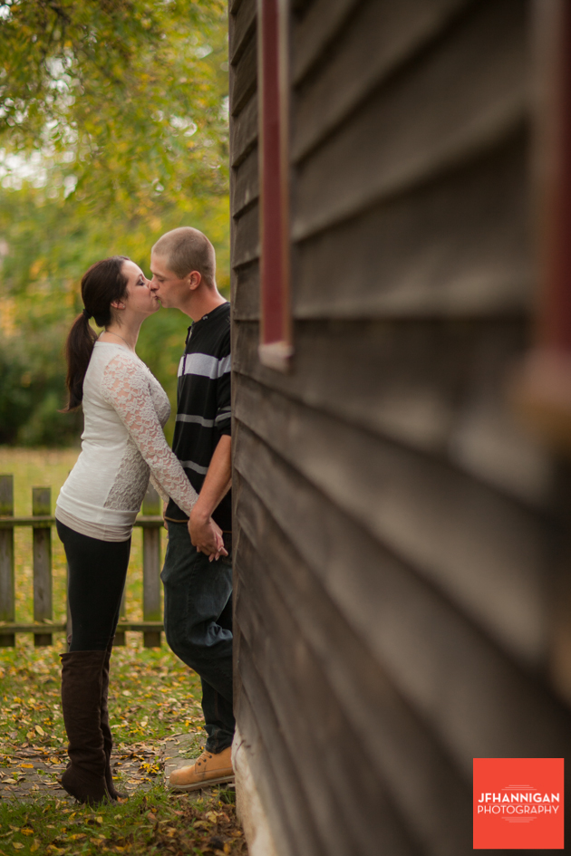 couple kissing fall leaves in background