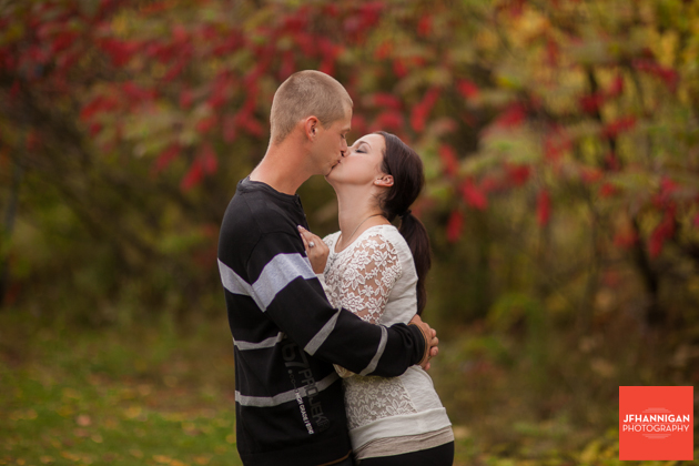 couple kissing with fall colors in background