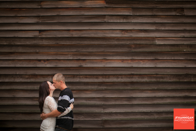 couple kissing wood barn in background