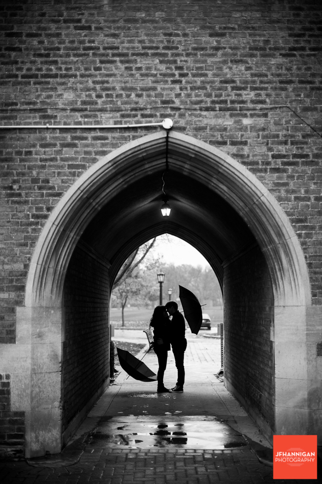 Black and white, Brick wall, archway, rain, umbrellas, Ridley College, Engagement Photo Shoot, Bride and Groom to Be, Niagara Wedding Photographer, Niagara Wedding Photography