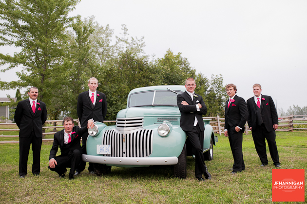 groom and ushers posed with green antique truck