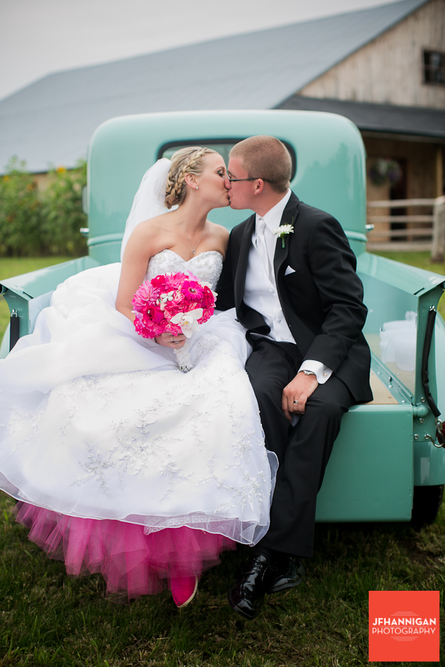 bride and groom sitting and kissing in back of antique truck