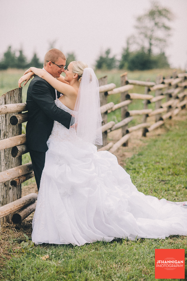 bride and groom embracing on log fence