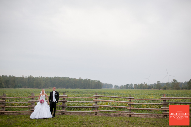 bride and groom posed in field with log fence in background