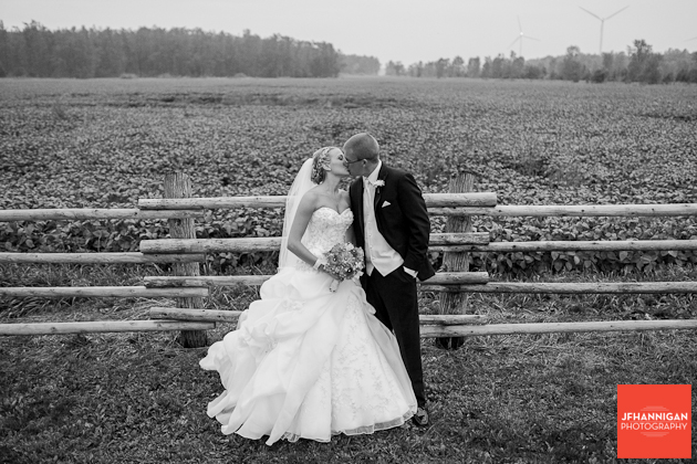 bride and groom kissing log fence in background