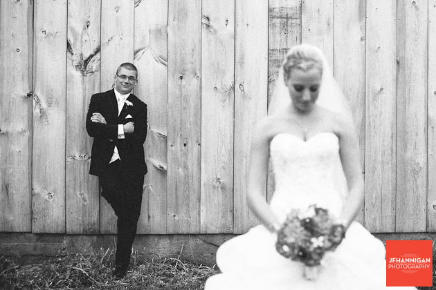bride in foreground groom leaning on barn wall