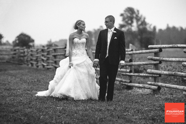 bride and groom walking in the field along log fence