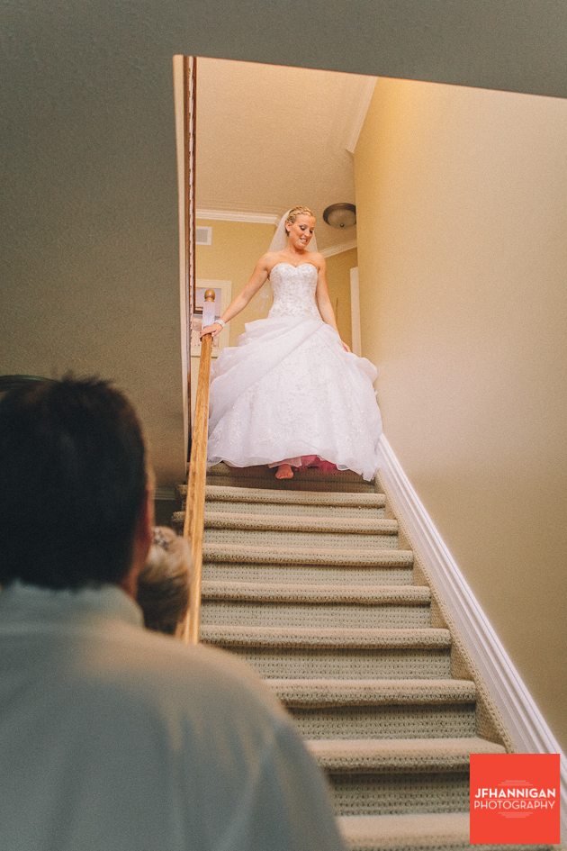 bride coming downstairs as father watches in foreground