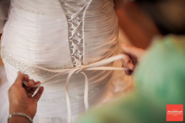 mother ties daughter's wedding dress