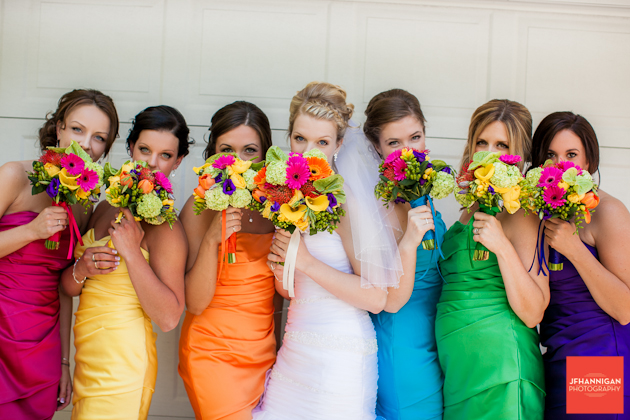bride and bridesmaids behind bouquets
