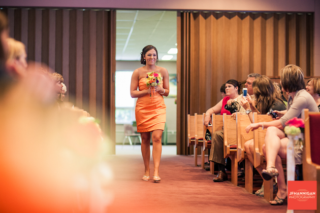 girl in orang dress walking down the aisle bridesmaid