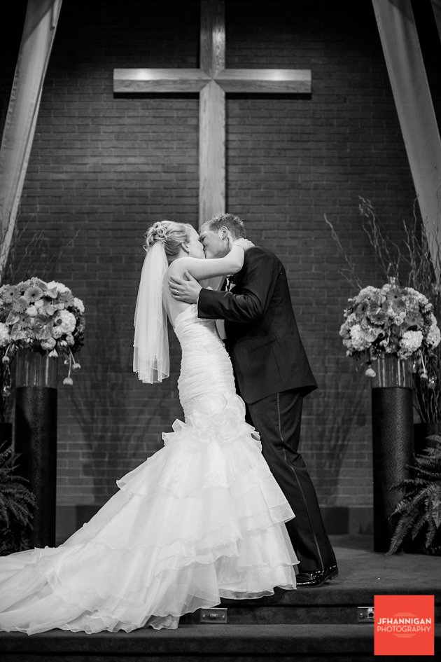 bride and groom kissing at wedding black and white