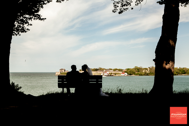 bride and groom on bench by waterfront silhouette
