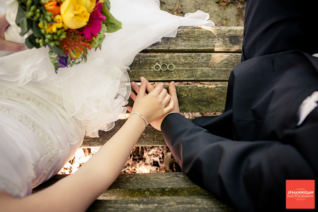 bride and groom holding hands on bench with rings