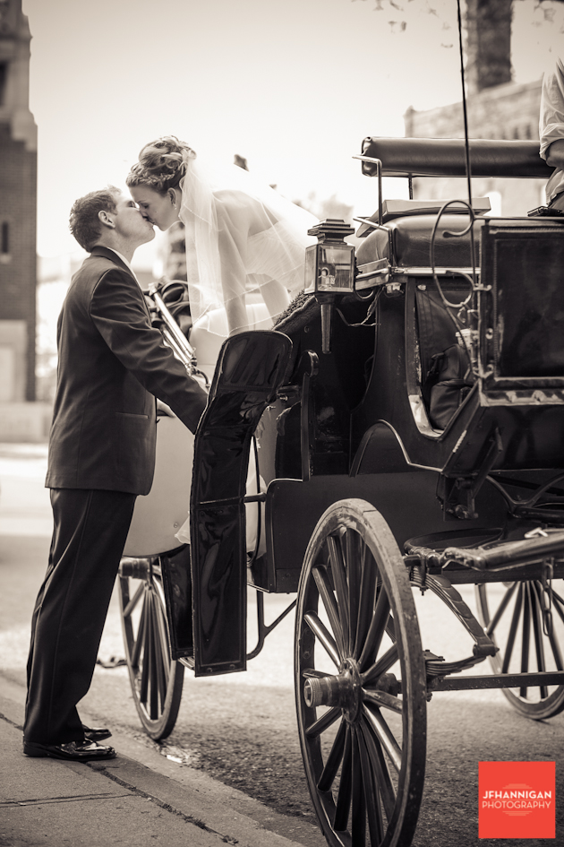 bride and groom kissing in carriage sepia