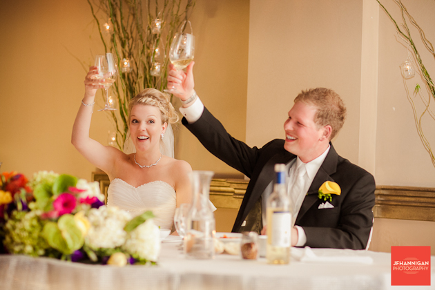 bride and groom holding up glasses