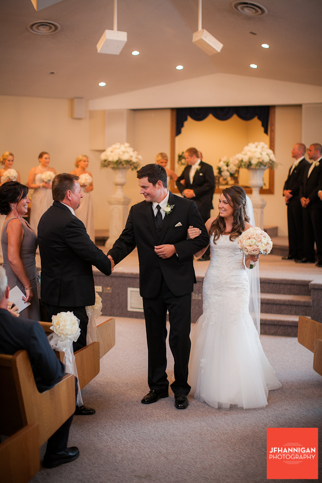 bride and groom greet parents while leaving the church