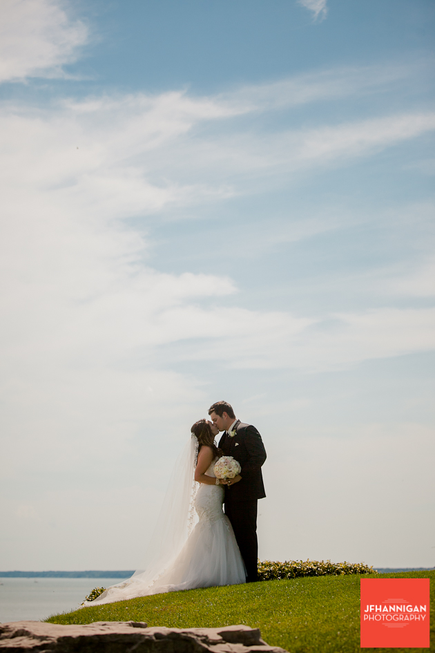 bride and groom kissing lake in background