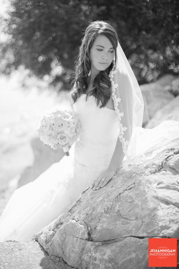 bride positione on rocks of shoreline