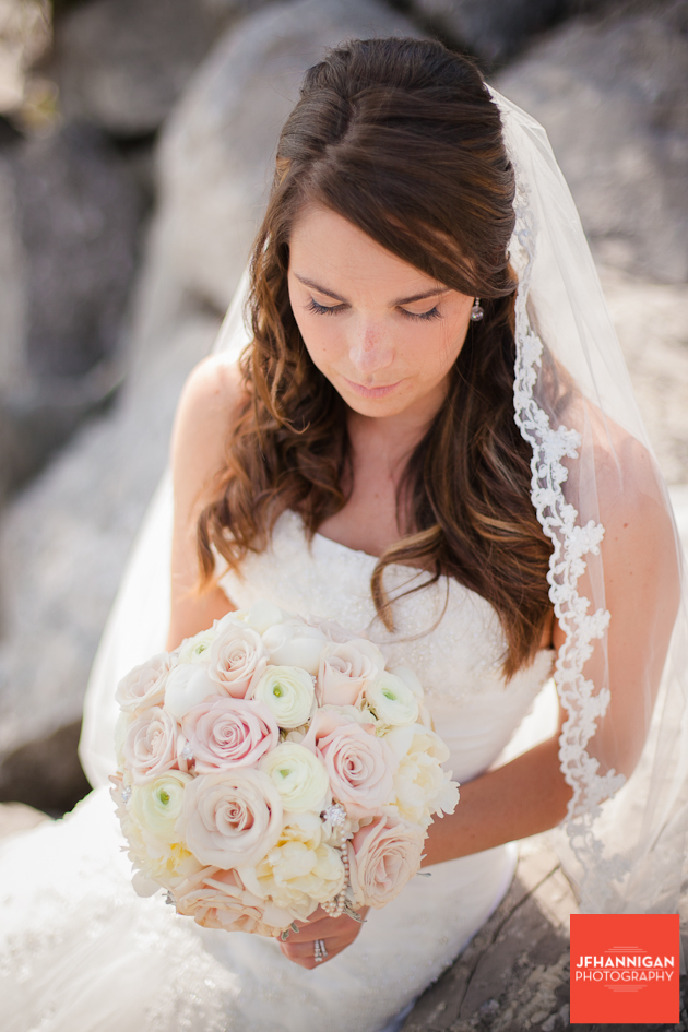 bride looking at bouquet while sitting on rocks of lake shore