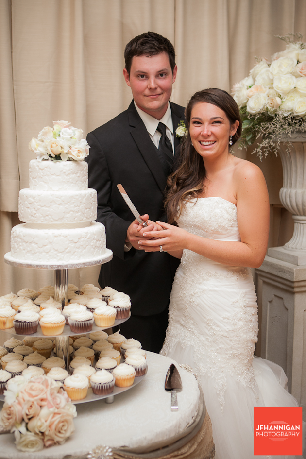 bride and groom posed ready to cut wedding cake