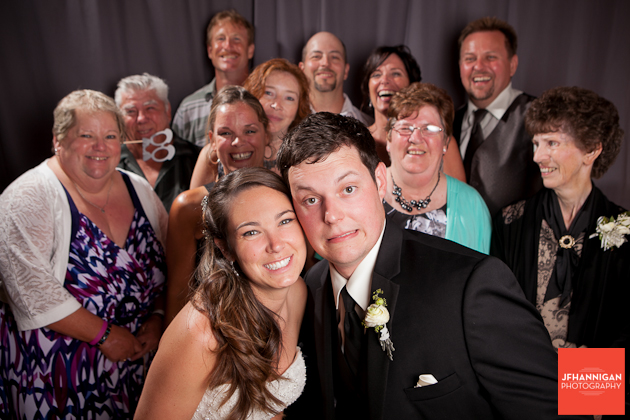 bride and groom in photobooth with guest
