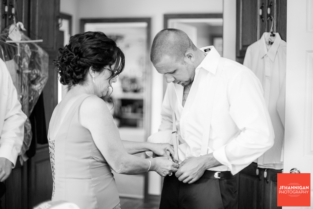 groom's mother helping with suspenders