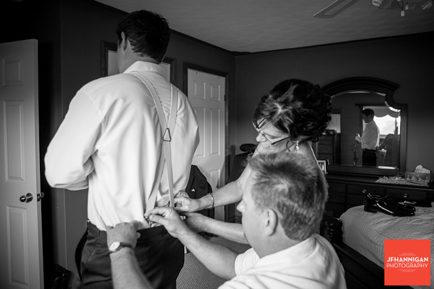groom's mom and dad helping with suspenders