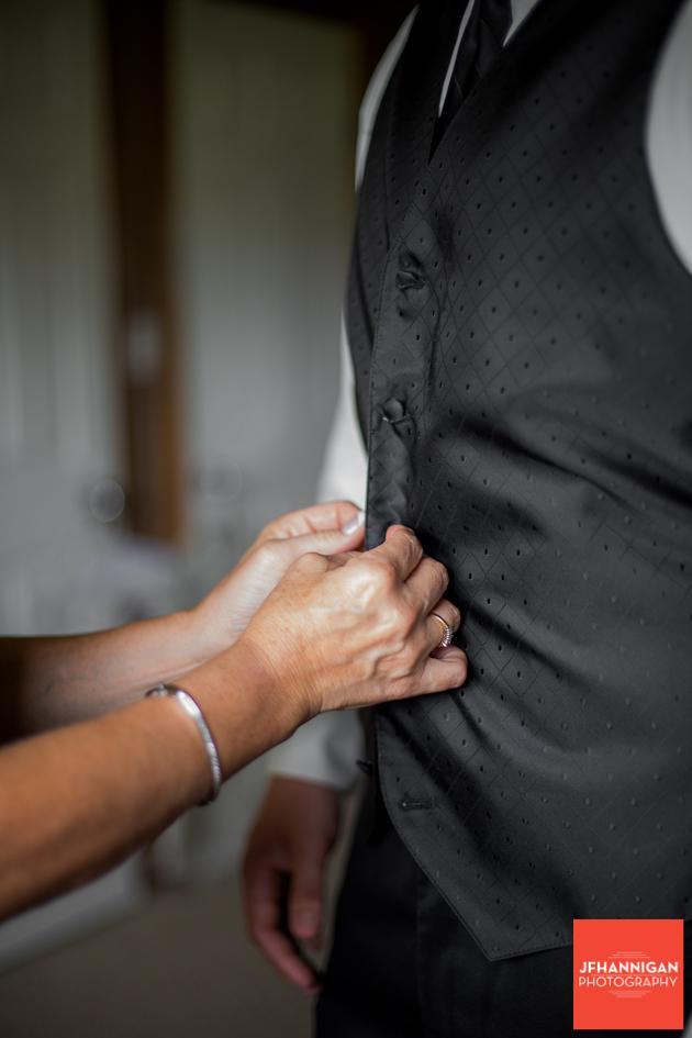 groom's mother buttoning vest