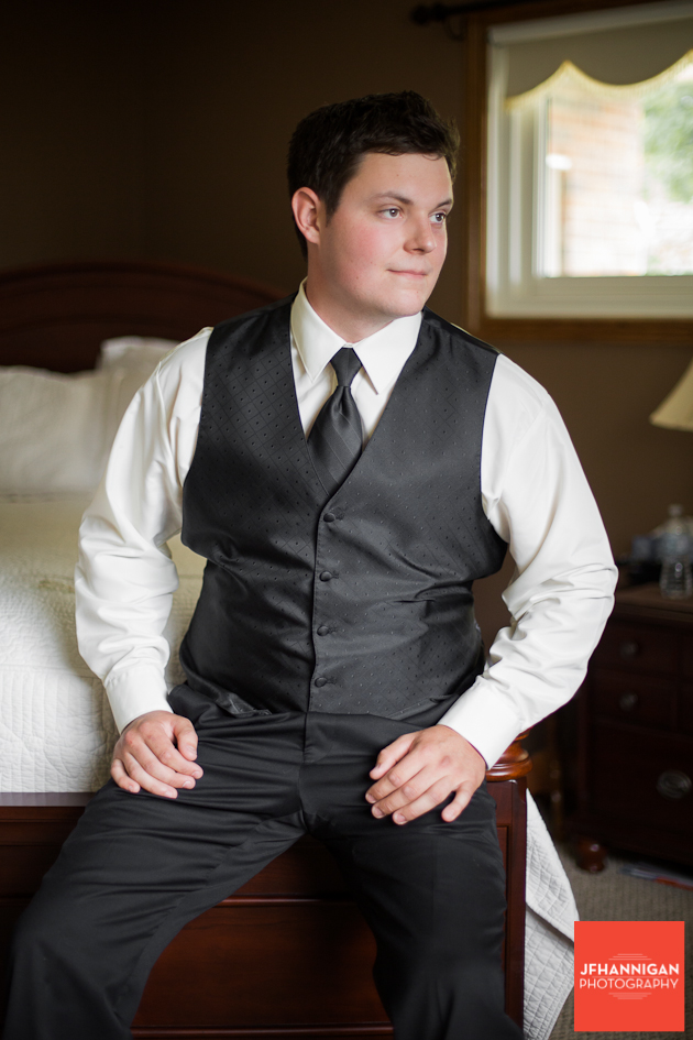 groom posed in bedroom