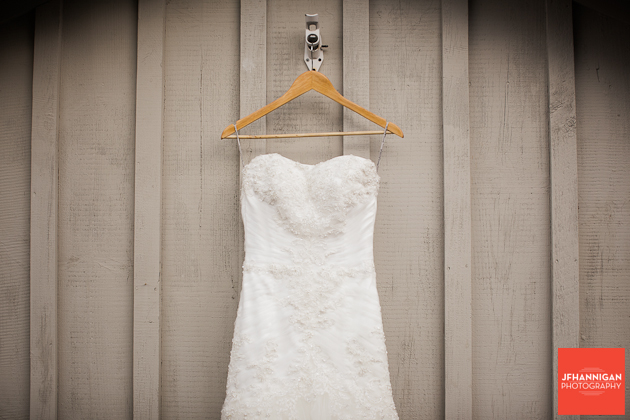 bridal gown hung on side of shed