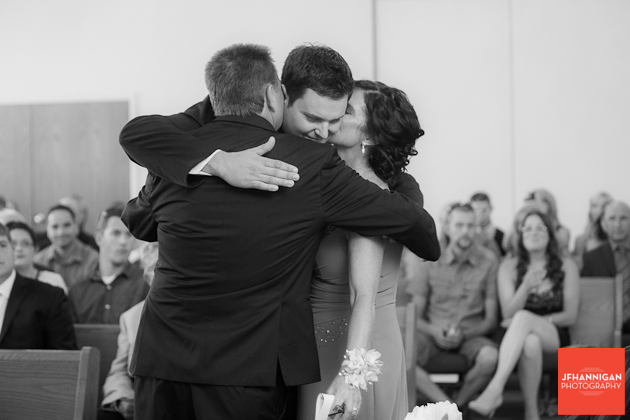 groom being kissed by mom and dad