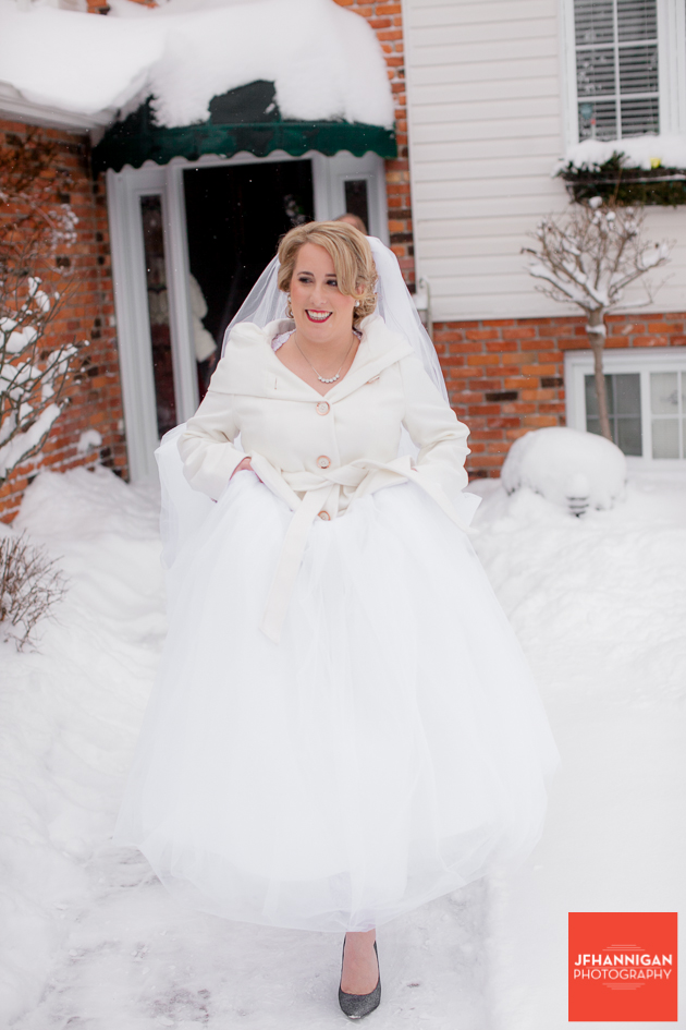 bride comes out of house on snowy day