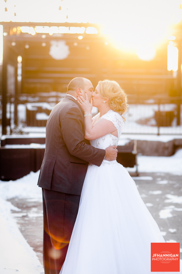 bride and groom kissing with sun beaming on them