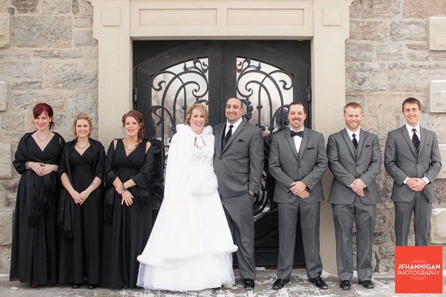 wedding party women in furs standing in front of iron doors with block wall