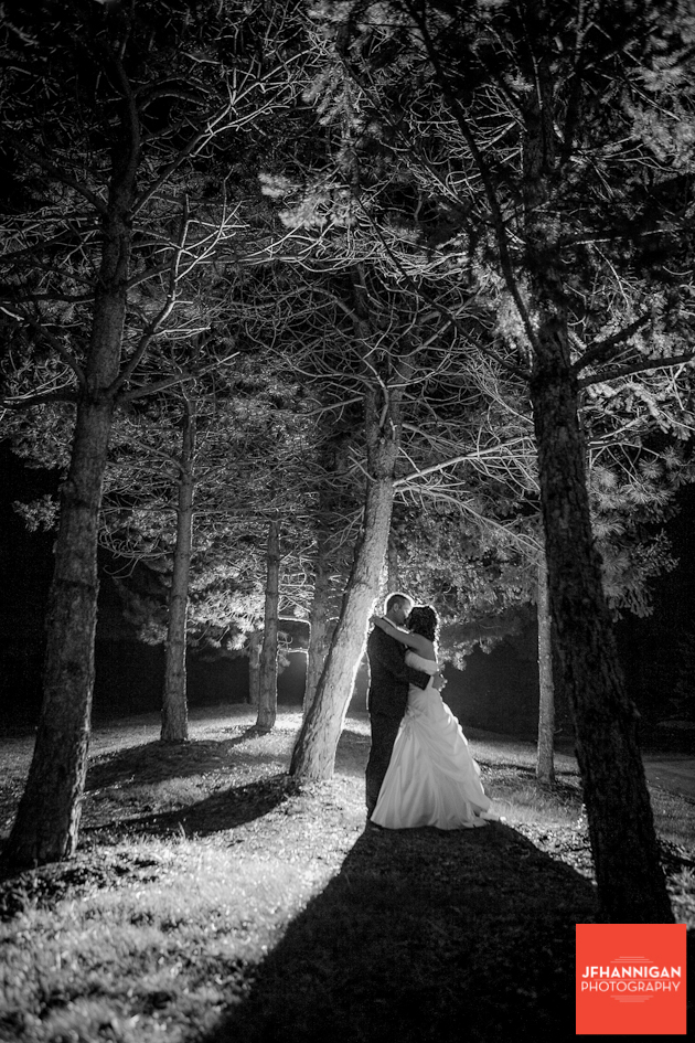 bride and groom kissing under trees at night with back light