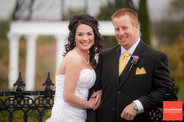 bride and groom in front of rod iron fence